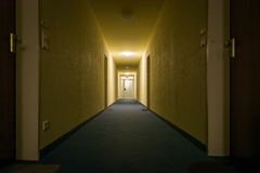 Dimly Light Corridor Hallway Apartment Complex Perspective Exit. Lit Eerie Yellow Architecture stock photography