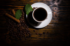 Dimly lit cup of coffee with leaves and beans Stock Photo