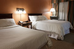 Dimly Lit Hotel Room With Two Beds. A dimly lit and small hotel room with two beds, brown walls, and white bedspreads Stock Photography