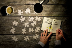 Dimly lit scene of hands writing 2017 with puzzle Royalty Free Stock Photos