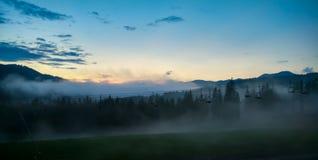Dimma i bergen på soluppgång Arkivfoton