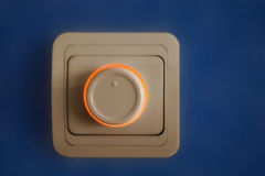 Dimmer. Electric switch on blue background Stock Image