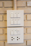 Dimmer switch and light switch on switchboard.over  brick wall Stock Photos