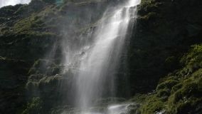 Dimmig bakbelyst vattenfall stock video