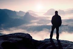 Dimmig dag i steniga berg Kontur av turisten med poler i hand Fotvandrareställning på stenig siktspunkt ovanför den dimmiga dalen Arkivfoton