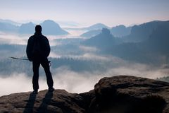 Dimmig dag i steniga berg Kontur av turisten med poler i hand Fotvandrareställning på stenig siktspunkt ovanför den dimmiga dalen Royaltyfri Bild