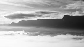 Dimmig dal, i morgonen, med berg och den molniga skyen Arkivbild