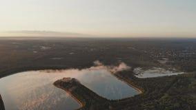 Dimmig gryning på den låga morgondimman täckte sjön i en skog lager videofilmer