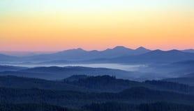 Dimmig morgon i bergen med konturer av kullar Serenitetsoluppgång med mjukt solljus och lager av ogenomskinlighet arkivfoto
