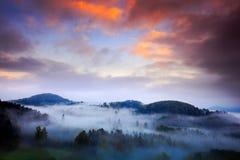 Dimmig morgon med härliga orange moln Den kalla dimmiga dimmiga morgonen i en nedgångdal av bohemmet Schweiz parkerar Kullar med  Royaltyfri Foto