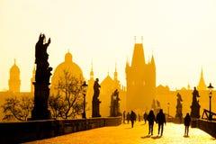 Dimmig morgon på Charles Bridge, Prague, Tjeckien Soluppgång med konturer av att gå folk, statyer och gammalt Arkivbild