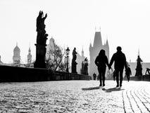 Dimmig morgon på Charles Bridge, Prague, Tjeckien Soluppgång med konturer av att gå folk, statyer och gammalt Arkivbilder