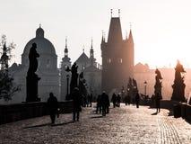 Dimmig morgon på Charles Bridge, Prague, Tjeckien Soluppgång med konturer av att gå folk, statyer och gammalt fotografering för bildbyråer