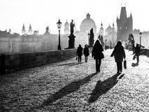 Dimmig morgon på Charles Bridge, Prague, Tjeckien Soluppgång med konturer av att gå folk, statyer och gammalt Royaltyfri Fotografi