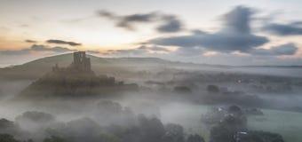 Dimmig morgonsoluppgång över slott fördärvar arkivbilder