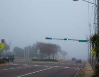 Dimmig ogenomskinlighetsmorgon i Florida med trafikbilar Arkivfoto