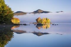Dimmig sjö och gröna berg - ön med färgrika träd - höst/nedgång - Vermont royaltyfri bild