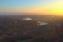 Dimmig soluppgång över floden Arkivfoto
