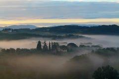 Dimmig soluppgång över Tuscan landshus Arkivbilder