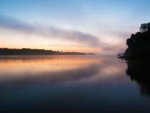 Dimmig soluppgång på en flod Arkivfoto