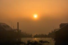 Dimmig vintersoluppgång över floden Arkivbild