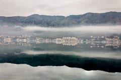 Dimmig weater på havet med bergreflexioner Royaltyfria Bilder