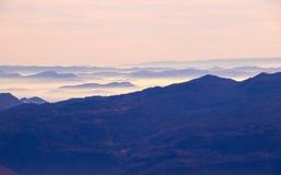 Dimmiga berg i morgonen Arkivfoton