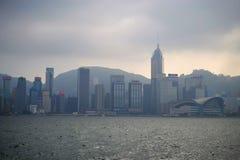 Dimmiga Hong Kong på Victoria hamn från Tsim Sha Tsui strand arkivbilder