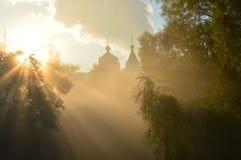 Dimmiga morgon- och sols strålar på templet Royaltyfria Bilder