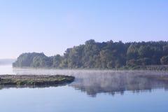 Dimmigt landskap med trädkonturn och reflexion på vatten på dimma på soluppgång. Försommarmorgon på den stillsamma sjön. Morgon sj Royaltyfri Bild