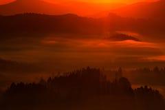 Dimmigt rött morgonlandskap Morgonlandspace med dimma Soluppgång i liggande Sol under soluppgång i den tjeckiska nationalparken C Arkivfoto