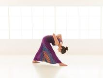 Dimostrazione di posizione di yoga dal giovane istruttore femminile Fotografie Stock