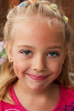 Dimples. A young happy little blond girl with big dimples in pink blouse, clips in her hair. Shallow depth of field Stock Photo