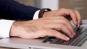 Dinámico enfocan adentro las manos del hombre que mecanografían rápidamente en el teclado de ordenador almacen de video