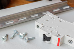 DIN rail, circuit breaker and the screws on the mounting plate Royalty Free Stock Image
