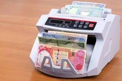 Dinar irakien dans une machine de compte image stock