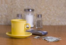 At the Diner. Brightly colored yellow cup of coffee and cellphone on a table at the diner. Dollar bills and change on the table. Sall, pepper, and a sugar jar stock photo