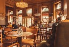 Diner binnen van donkere ruimte van historische koffie met sprekende mensen en uitstekend meubilair Stock Afbeelding