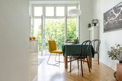 Diner des chaises autour d'une table en bois sur un plancher de parquet en arête de poisson d'une cuisine blanche avec le balcon  images libres de droits