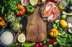 Diner die ingredints koken Ruwe ongekookte zalmvissen met groenten, rijst, kruiden en kruiden over rustieke houten stock afbeelding