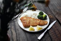 Diner. Fish in breadcrumbs fried with rice and broccoli stock photos