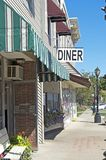 Diner Sign and Downtown Frontage. Diner sign jutting out from the front of a row of businesses on a small town downtown main street Royalty Free Stock Image