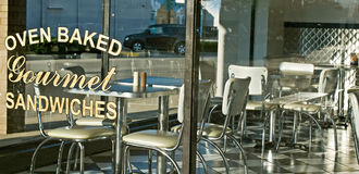 Diner Window with Tables & Chairs. Retro 1950s style diner window with stainless steel tables & chairs Royalty Free Stock Photo