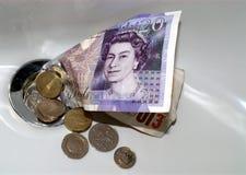 Dinero abajo del dren imagen de archivo
