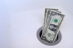 Dinero abajo del dren Foto de archivo