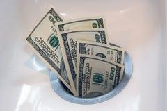 Dinero abajo del dren fotografía de archivo