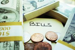 Dinero apilado encima de representar las cuentas que necesitan ser pagadas imagen de archivo libre de regalías
