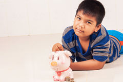 Dinero asiático del ahorro del muchacho en piggybank Imagen de archivo libre de regalías