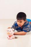 Dinero asiático del ahorro del muchacho en piggybank Foto de archivo