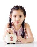 Dinero asiático del ahorro de la niña en una hucha Aislado en el fondo blanco Imagen de archivo libre de regalías